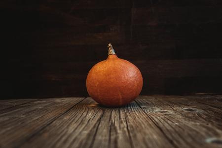 Orange pumpkin with fresh raw fruit on a wooden board
