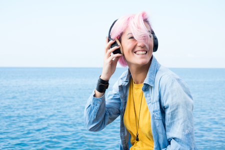 Portrait of beautiful girl sitting on rock near the sea in the headphones listening to music, with fuchsia hair
