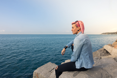 beautiful girl looks at the horizon on the rock, with fuchsia hair