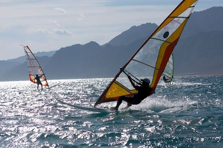 three windsurfers in patches of light of a sunlight