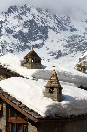 Snow roofs and chimneys on a background of mountains 스톡 사진