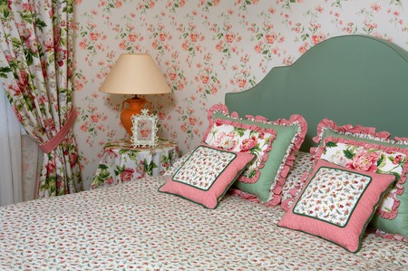 Interior of a bedroom with a lamp pillows a vegetative ornament