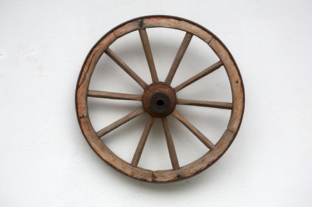 Old wheel of a cart on a white wall