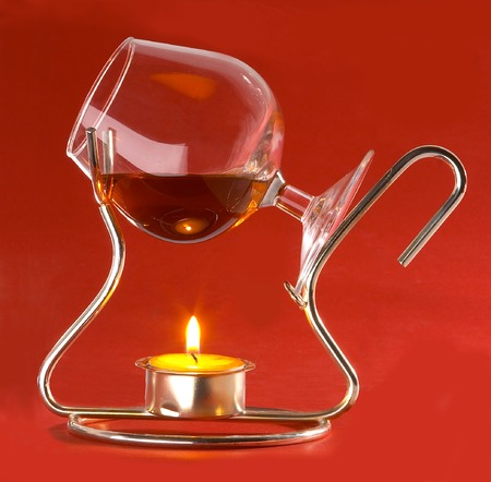 glass with cognac and candles