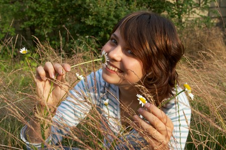 The smiling girl with a camomile flower Stock Photo - 4251915