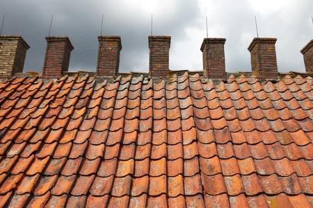 flue season: Techo de tejas de una antigua casa de humo para los peces con un conjunto de tubos