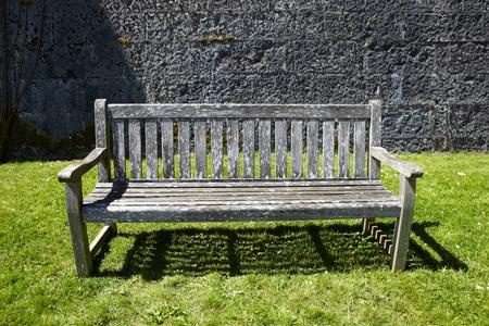 garden bench: Vintage, wooden garden bench against stone wall