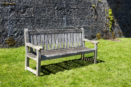 Vintage, wooden garden bench against stone wall photo