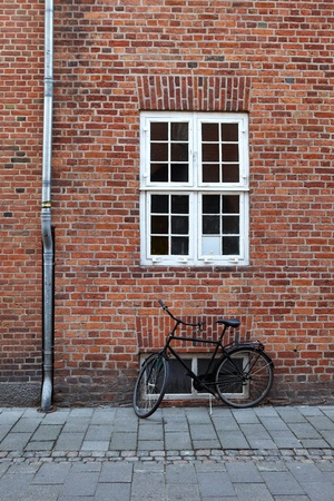 parked bicycles: Black bicycle from an old brick wall with a window and downspout