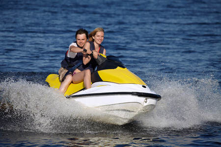 Happy smiling caucasian couple riding jet ski photo