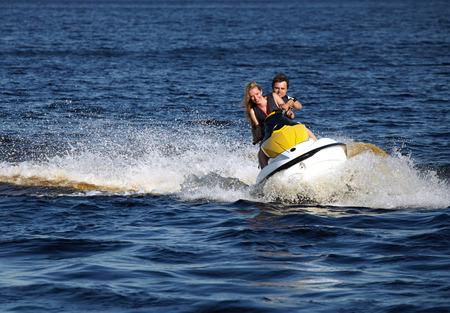 moto acuatica: Feliz pareja sonriente caucásica montar jet ski Foto de archivo