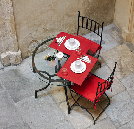 Street served red napkin forged table and chairs Stock Photo