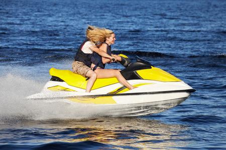 personal watercraft: Happy smiling caucasian couple riding jet ski