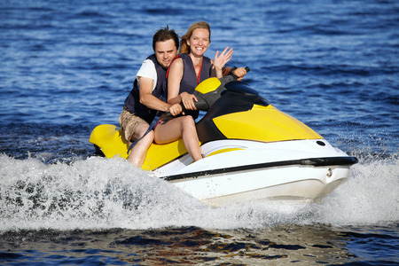 Happy smiling caucasian couple riding jet ski