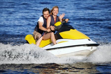 Happy smiling caucasian couple riding jet ski