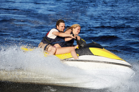 water skiing: Happy smiling caucasian couple riding jet ski
