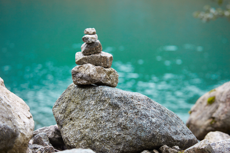 cairn: Cairn on the shore of a mountain lake in Norway