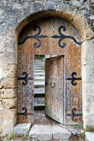 Ajar old wooden door in stone arch Standard-Bild