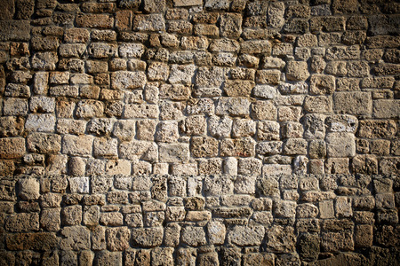 Ancient stone wall of the amphitheater in Caesarea as background
