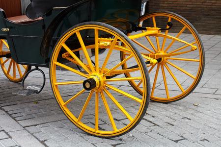 sevilla: Yellow wheel olden horse carriage on the cobblestones Spain. Sevilla