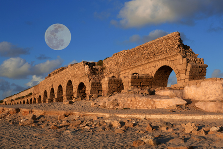 Aqueduct in Caesarea at sunset with a full moon