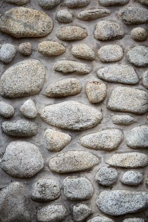 Stones background, gray large stones, boulders in the masonry, part of stone fence, close-up of stone border