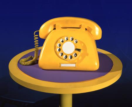 Vintage yellow sham phone on blue background