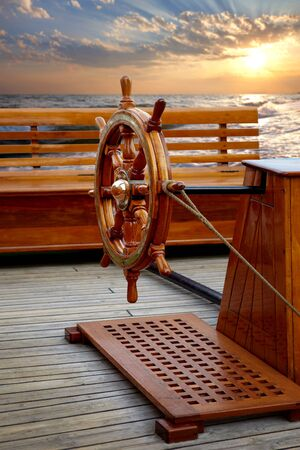Old wooden ships helm on background of sea sunset Banque d'images