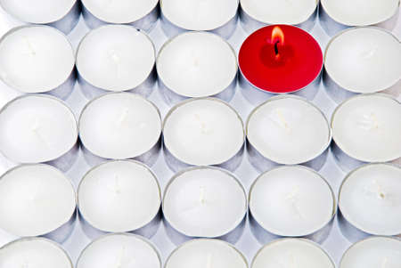standout: One red candle among lots of white candles Stock Photo