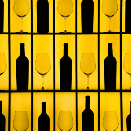 Black bottles and crystal glasses with a yellow backlight