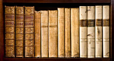 Ancient books (XVI and XVII century) on a wood shelf photo