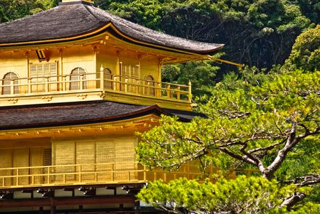 Close up of Kinkaku-ji temple, a Zen Buddhist sanctuary in Kyoto, Japan. The top two stories of the pavilion are covered with pure gold leaf.