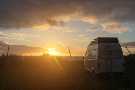 Oldtimer campervan parking at the ocean while the sun sets on the horizon casting a warm light on the scene with birds passing by.