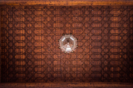 Pattern of wooden tiles on the ceiling of an old building.The lamp in the middle is slightly rotated, which destroys the symmetrical structure  of the whole texture giving it an uneasy feeling. Stock Photo