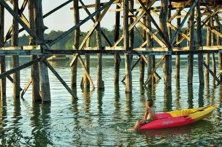 bridge in nature: A boy on kayak in Sangklaburi, Karnjanaburi province, Thailand