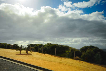 Bench beside road with blue sky in Great Ocean Road route