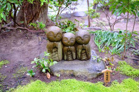 Jizo-sculptuurpop (kleine Japanse boeddhistische monnikspoppenrots) in Japanse tuin Stockfoto