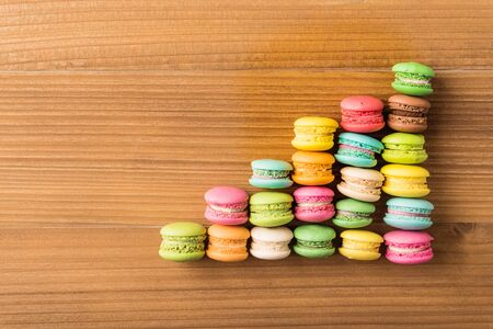 Colorful French macaron top view arrange in graph shape on wood background
