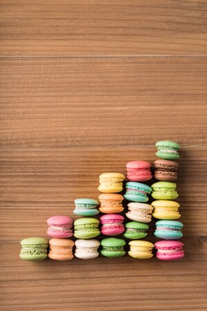 Colorful French macaron top view arrange in graph shape on wood background 스톡 콘텐츠