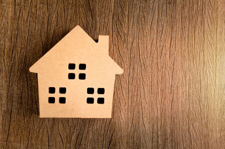 Wooden home model in vintage tone on wood background