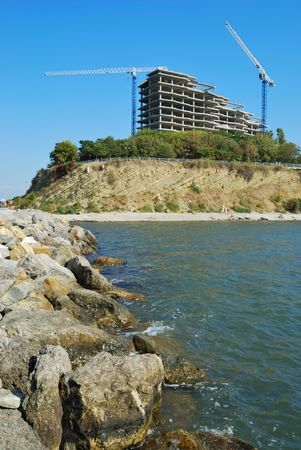 housebuilding: modern monolithic housebuilding and cranes on coast of Black sea Stock Photo