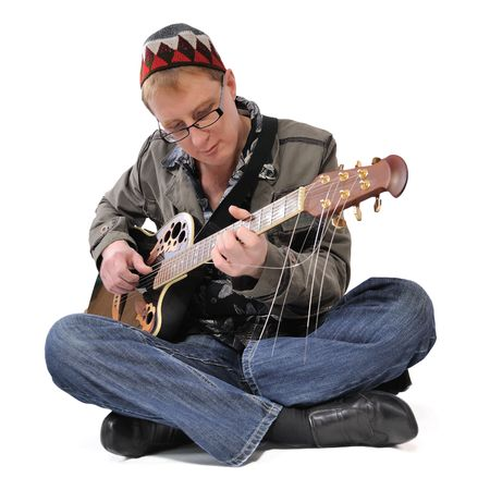 The man sitting on floor and playing guitar