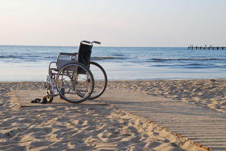 Wheelchair on sandy seacoast.