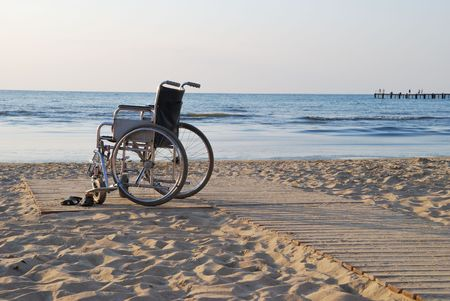 Wheelchair on sandy seacoast.