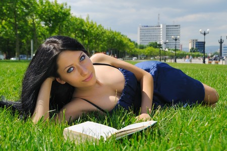 Girl reading a book outdoors in summertime.