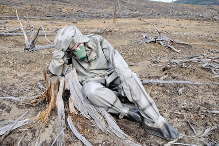 The person in protective suit in the dead forest Stock Photo