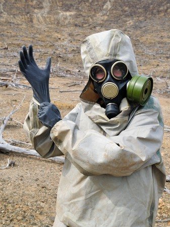 The person in chemical protection suites puts on gloves photo