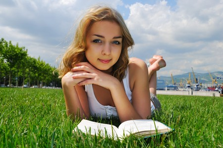 Girl reading a book outdoors in summertime. Looking at camera photo