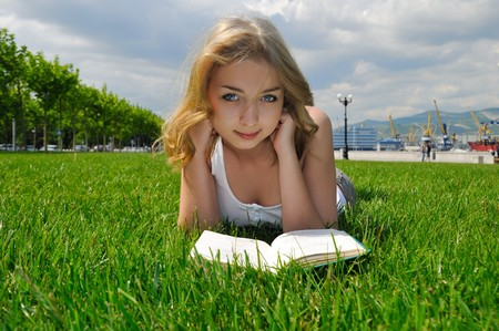 Girl reading a book outdoors in summertime. Looking at camera Stock Photo - 8152763