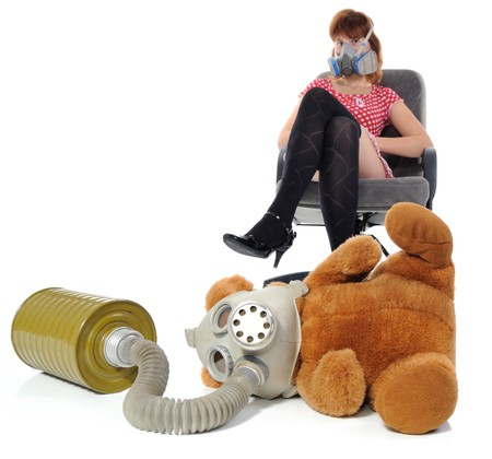 The girl sitting in an armchair and soft toy with gas mask